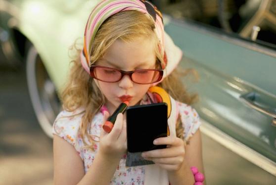 Young girl applying lipstick